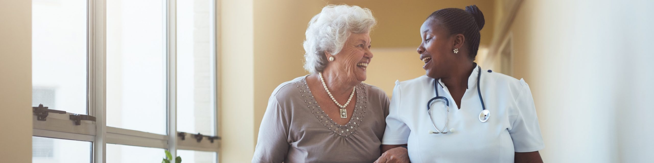 Portrait of smiling healthcare worker walking and talking with senior woman. Happy elder woman gets help from nurse for a walk through nursing home.