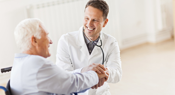 Patient in wheelchair interacting with doctor.