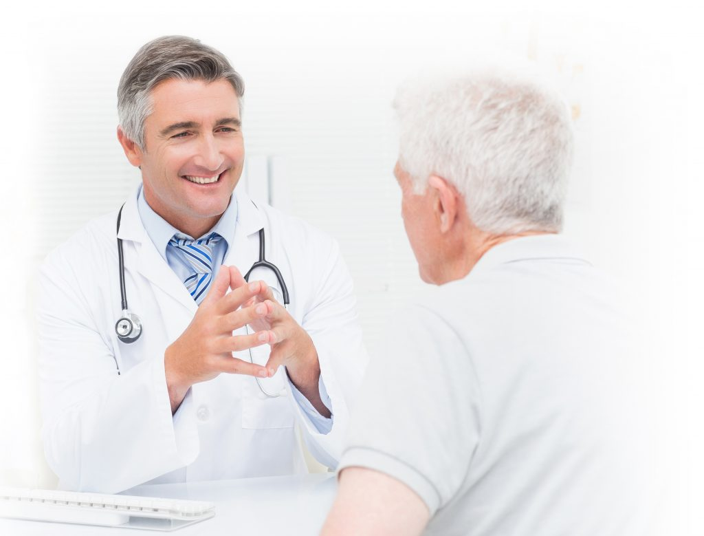 Male doctor discussing with senior patient in clinic