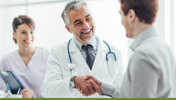 smiling doctor shakes hands with patient